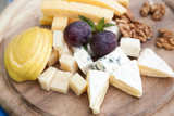 Cheese platter with grapes and selective focus