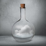 Glass bottle with liquid and vapor standing inside gray box
