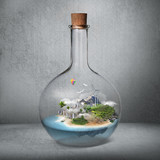 Corked glass bottle with beautiful island and sea inside. Microc