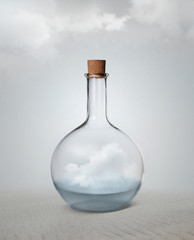 Small vintage glass bottle with water and cloud inside standing