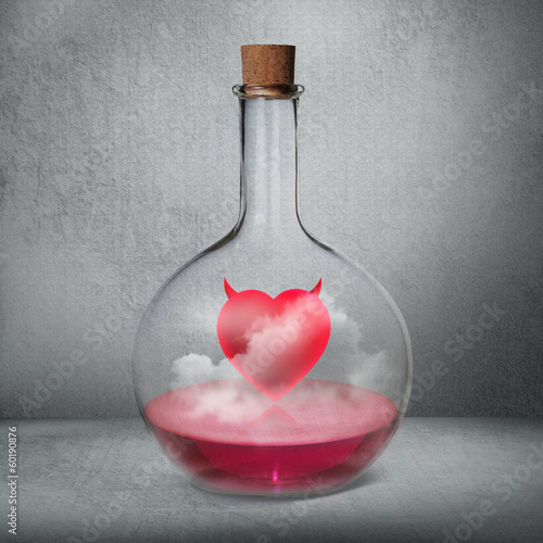 Glass bottle with philtre and love potion standing inside gray b