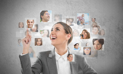 Young successful business woman looking at people portraits. Int