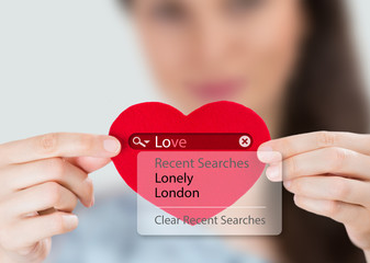 Love search. Young woman holding red heart with love search opti