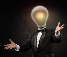 Businessman with lamp head on black background