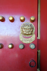 red gate with a gold in the forbidden city in Beijing, China