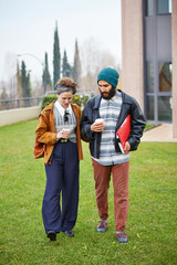 Hipster couple talking and drinking coffee to go