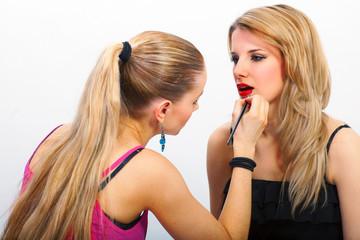 Make-up artist applying mascara on lips