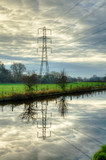 Electricity pylon reflected in water