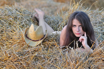 Nude girl lies on senovalle near cowboy hat
