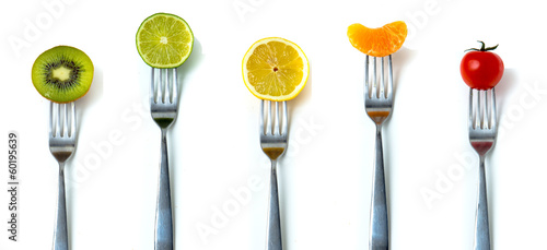 MIx of fruits and vegetables on forks in white background