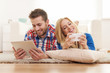 Happy couple spending time with electronic equipment at home