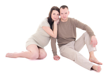 young pregnant couple sitting isolated on white background