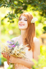 Redhead girl with flowers at outdoor.