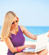 Blonde girl with notebook at the beach.
