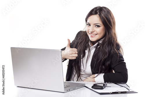 Leinwanddruck Bild smiling  business woman at desk with laptop showing thumbs up