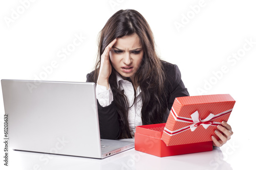 disappointed young business woman at the desk opens a box