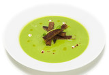 pea soup with croutons on a white dish at restaurant