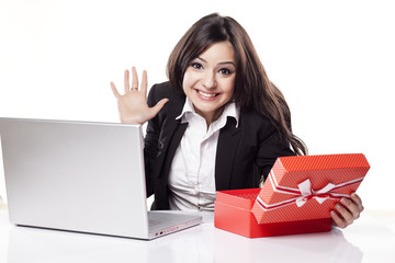 happy woman at the desk with a laptop opens a box with a gift