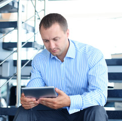 businessman sitting on stairs with electronic tablet