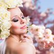 junge Frau mit Rosenkopfschmuck vor Kirschblütenhintergrund