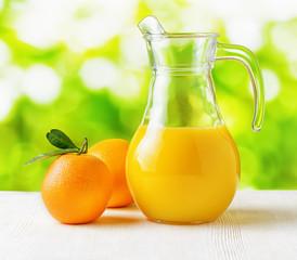 Jug of orange juice on nature background