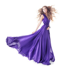 Woman in purple silk waving dress walking over white background
