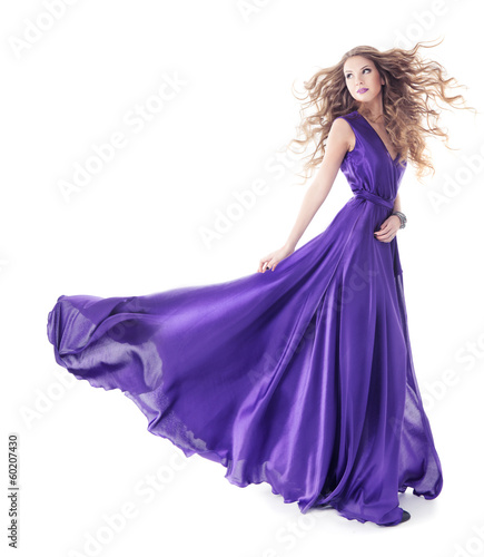 Woman in purple silk waving dress walking over white background