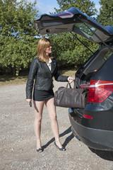 Woman loading overnight bag into car