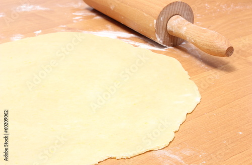 Sheeted yeast cake and rolling pin on wooden table