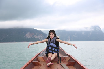 attractive woman on bow of boat with mountain and sky
