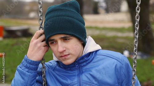 Sorrowful teenage boy swinging in the park episode 1