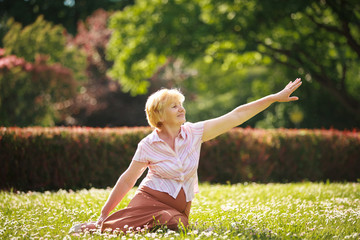 Meditation. Graceful Old Woman in the Park Stretching her Hand