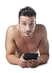 Handsome young man shirtless reading ebook on the floor