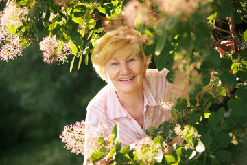 Lively Cheerful Optimistic Senior Woman among Flowers