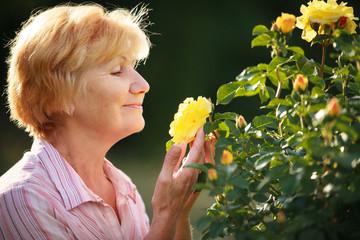 Expression. Senior Woman Model with Garden Roses. Springtime