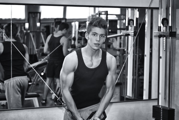 Teen bodybuilder working out with gym equipment