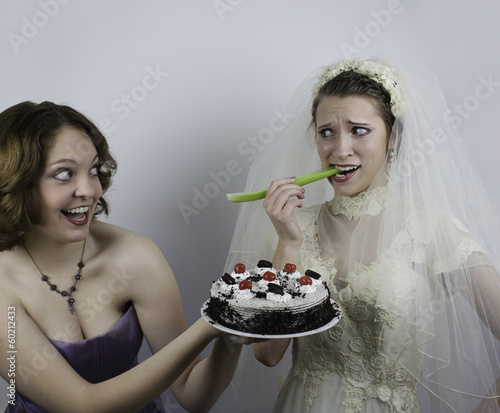 Young bride is being tempted by bridesmaid holding a cake