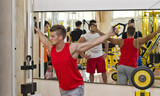 Young man training pecs on gym equipment poster