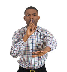 Portrait young serious businessman finger on lips saying quiet