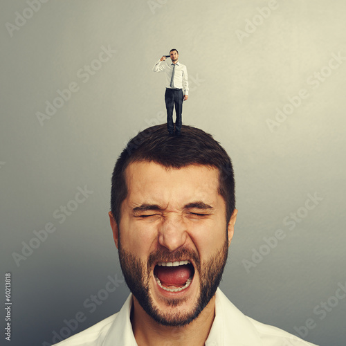 small man with gun holding on the head