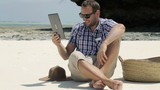 Young man on exotic beach chatting on tablet computer