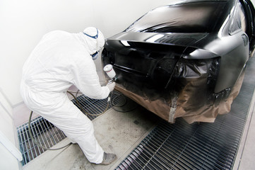 Worker painting a car in garage using an airbrush gun