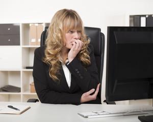 Beautiful businesswoman reading her monitor