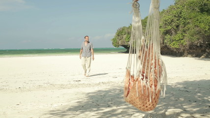 Happy man walking on beautiful exotic tropical beach