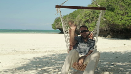 Young happy man on hammock waving hand to camera on exotic beach