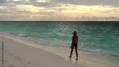 Girl is walking along the seashore. Maldives.