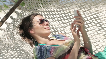 Young woman texting, sending sms on smartphone, lying on hammock