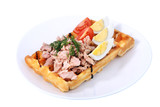 Belgian waffle with ham, boiled egg and tomato on white.