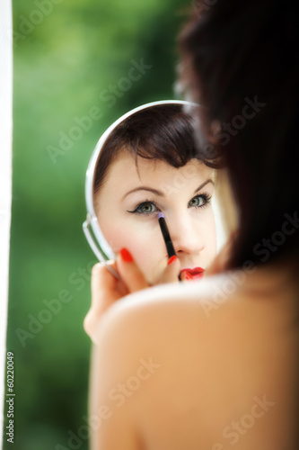girl applying make up reflection in mirror