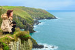 Woman sitting on rock cliff looking to ocean Co. Cork Ireland
